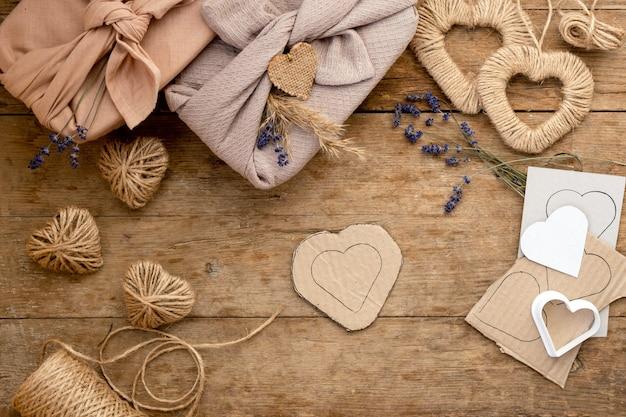 Null verschwenden valentinstag konzept und verspotten. geschenkverpackter furoshiki-stil mit lavendel, pampasgrasjute und schablonenherzen. draufsicht oder flache lage. anleitung, schritt für schritt