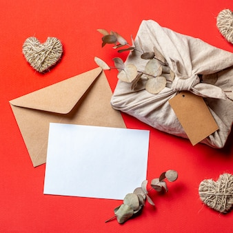 Nullabfall valentinstagkonzept auf rot. umweltfreundlicher geschenkstoff, der in furoshiki-art, kraftpapierumschlag, leere grußkarte einwickelt. ansicht von oben nach unten oder flach legen. kopieren sie platz für design