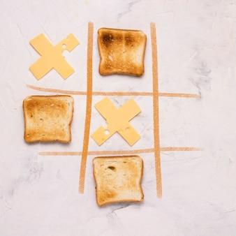 Nullen und kreuze, auswahl, spielwettbewerb der kreuze aus käse und square toasted toast white stone. flache lage, draufsicht