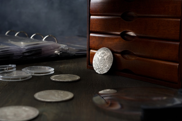 Numismatik. alte sammlermünzen aus silber, gold und kupfer auf einem holztisch.