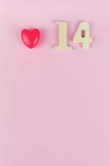 Nummer 14 gegen rosa wand. valentinstag-konzept. datum 14. februar.
