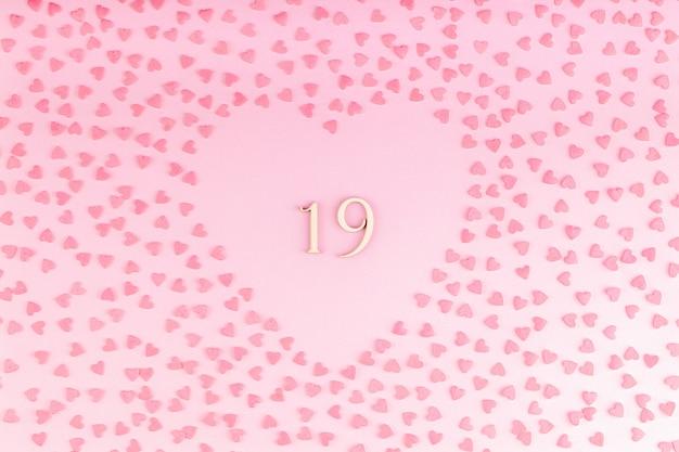 Nummer 19 neunzehn aus holz in herzförmiger dekoration mit kleinen herzen