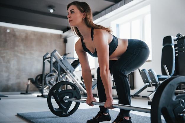 Nummer 20 auf der langhantel. foto der herrlichen blonden frau im fitnessstudio zu ihrer wochenendzeit