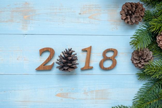 Nummer 2018 mit weihnachtsdekorationen auf hölzernem hintergrund