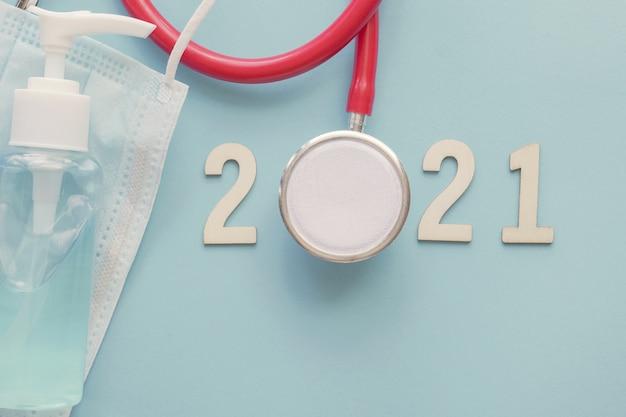 Nummer 2021 aus holz mit rotem stethoskop, gesichtsmaske und händedesinfektionsmittel