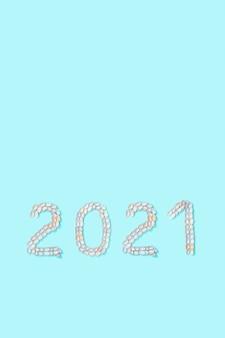 Nummer 2021 aus weißen und zartrosa muscheln auf türkisfarbenem papier sommerdesignkonzept