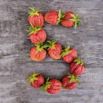 Nummer 5 der erdbeeren auf holzhintergrund