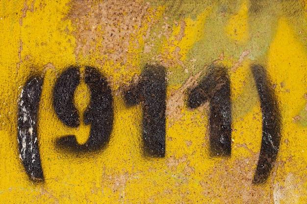 Nummer 911 auf einer alten gelben steinmauer