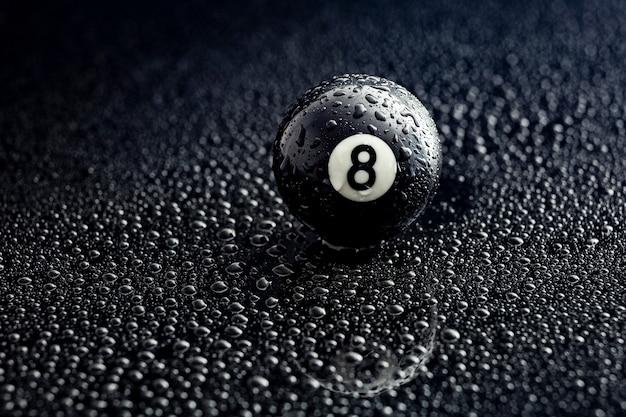 Nummer acht billardkugel mit wassertropfen auf einem schwarzen