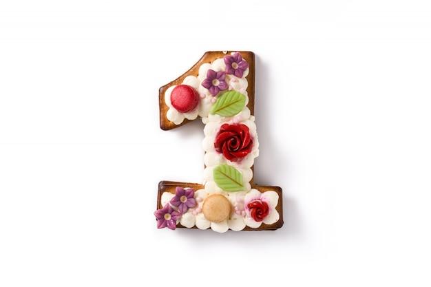 Nummer eins kuchen dekoriert mit blumen und macarons isoliert