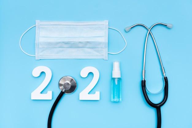 Nummer mit stethoskop, medizinischer maske und alkoholspray auf blau