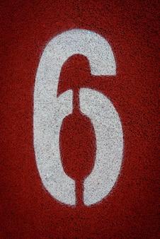 Nummer sechs auf dem start einer laufbahn im stadion