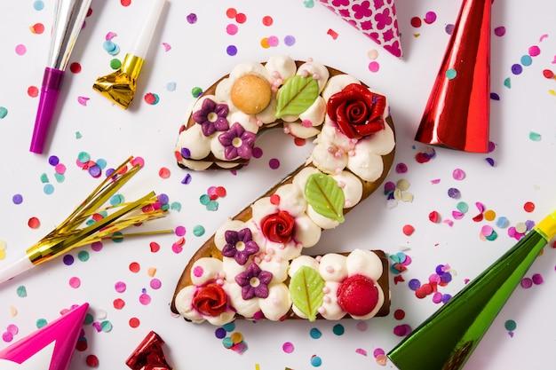 Nummer zwei-kuchen, dekoriert mit blumen, macarons und konfetti, isoliert auf weiss
