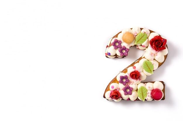 Nummer zwei-kuchen verziert mit den blumen und macarons, die auf weißem oberflächenkopienraum lokalisiert werden