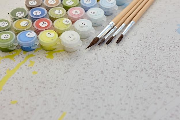 Nummerierte behälter mit farben und pinseln auf leinwand