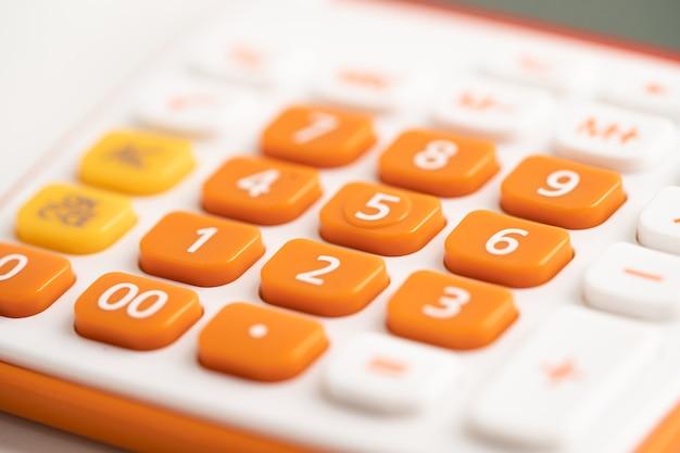 Nummernblock auf orangefarbenem taschenrechner für die kontofinanzierung im büro.