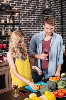 Nur ehepaar. frisch verheiratetes, gutaussehendes paar, das rotwein trinkt und zu hause zusammen kocht
