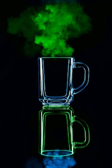 Nur ein glas auf einem schwarzen hintergrund mit einer reflexion. blau und grün mit dampf. isoliert.