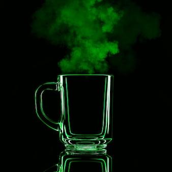 Nur ein glas auf einem schwarzen hintergrund mit einer reflexion. grüne farbe mit dampf. isoliert.