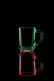Nur ein glas auf einem schwarzen hintergrund mit einer reflexion. rot und grün. isoliert.