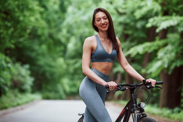 Nur eine person. weiblicher radfahrer, der mit fahrrad auf asphaltstraße im wald am tag steht