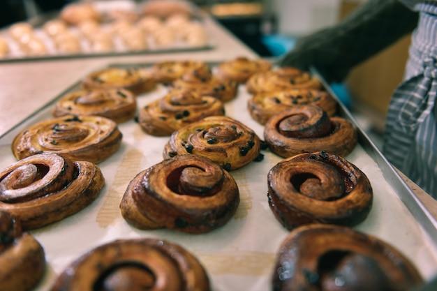 Nur gebacken. draufsicht von gerade gebackenen köstlichen zimtbrötchen mit rosinen, die in der bäckereiküche stehen