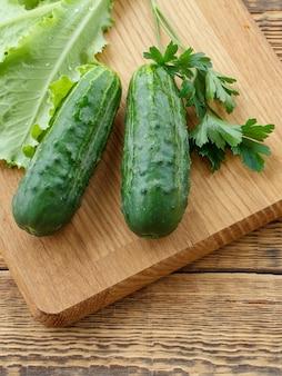 Nur gepflückte gurken und grüner salat auf schneidebrett und alten holzbrettern. gerade geerntetes gemüse. ansicht von oben.