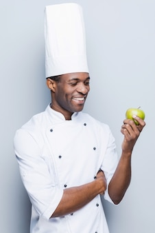 Nur gesundes essen kochen. selbstbewusster junger afrikanischer koch in weißer uniform mit grünem apfel