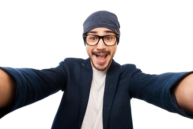 Nur ich! fröhlicher junger mann in brille und hut, der selfie macht, während er vor weißem hintergrund steht