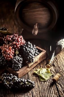 Nur reife trauben lose in einer holzkiste, im hintergrund ein weinfass und eine flasche rotwein.