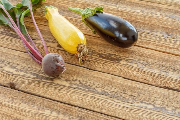 Nur rote beete, kürbis und auberginen auf alten holzbrettern gepflückt. habe gerade reifes gemüse geerntet. ansicht von oben.