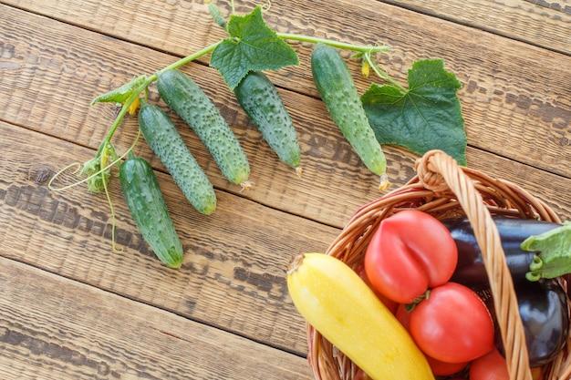 Nur tomaten, gurken, auberginen und kürbis im weidenkorb auf alten holzbrettern gepflückt. gerade geerntetes gemüse. ansicht von oben. Premium Fotos