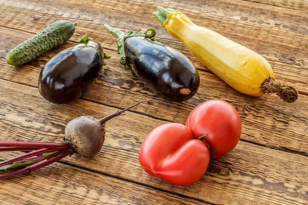Nur tomaten, rote beete, gurken, auberginen und kürbis auf alten holzbrettern gepflückt. habe gerade reifes gemüse geerntet. ansicht von oben.