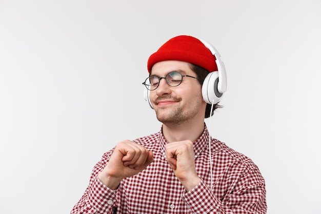 Nur vibing. glücklicher sorgloser junger hipster-typ mit schnurrbart in gläsern und roter mütze, die freudig tanzen und lieblingslied in kopfhörern mit erfreutem entspanntem gesicht, stehender weißer wand hören