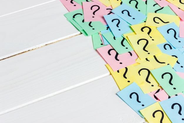 Nur viele fragezeichen auf farbigem papier auf holz