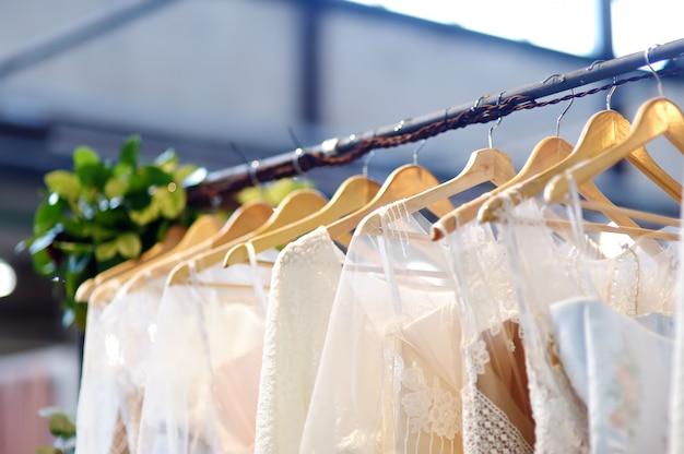 Nur wenige elegante hochzeits-, brautjungfern-, abend-, ballkleid- oder ballkleider auf einem kleiderbügel in einem brautgeschäft.