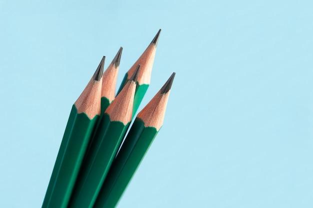 Nur wenige klassische, scharf angespitzte bleistifte aus graphit in grüner holzschale.