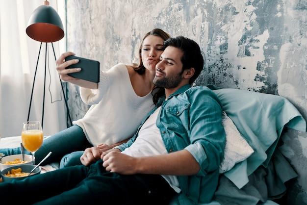 Nur zum spaß. schönes junges paar, das selfie macht und gesichter macht, während es zeit im bett zu hause verbringt