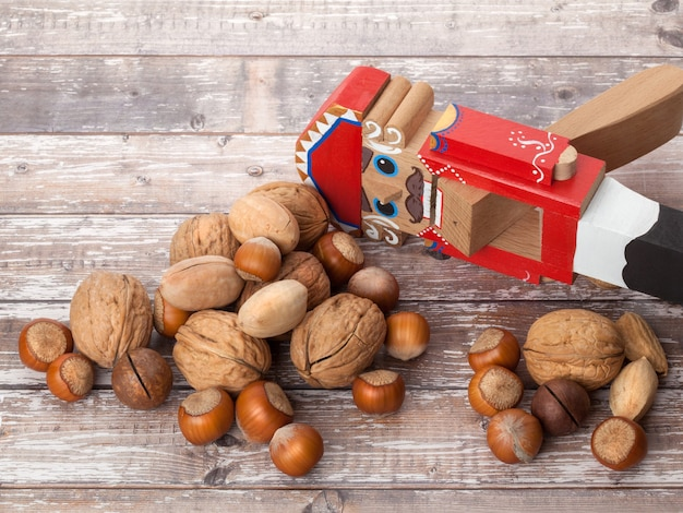 Nussknacker-holz-weihnachtsspielzeug mit schalennüssen auf holzuntergrund mit kopierraum