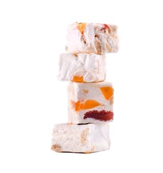 Nussnougat mit getrockneten früchten, süße süßigkeit lokalisiert auf weißem raum