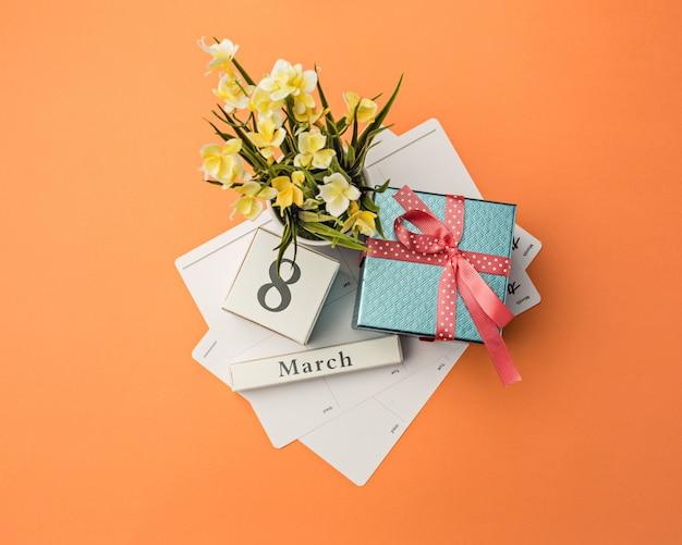 Oange schreibtisch mit geschenk, blumen und notizbuch