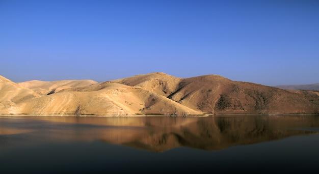 Oase mitten in der wüste - reflexion der wüstenberge auf der seeoberfläche