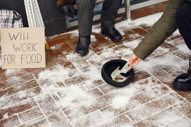 Obdachlose in einer winterstadt. mann, der um essen bittet.