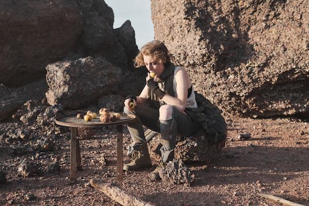Obdachlose junge frau, die auf dem felsen sitzt und draußen kartoffeln isst