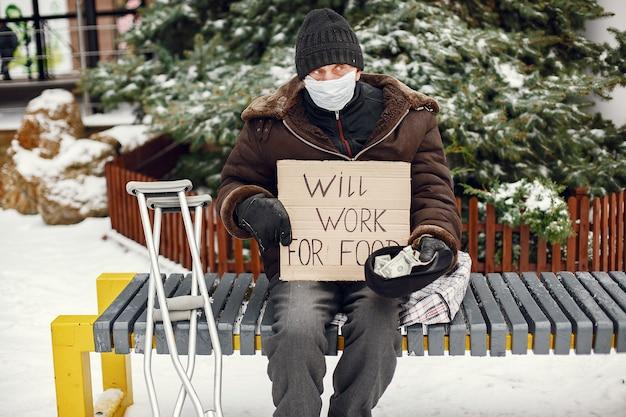 Obdachlose sitzen auf einer bank.
