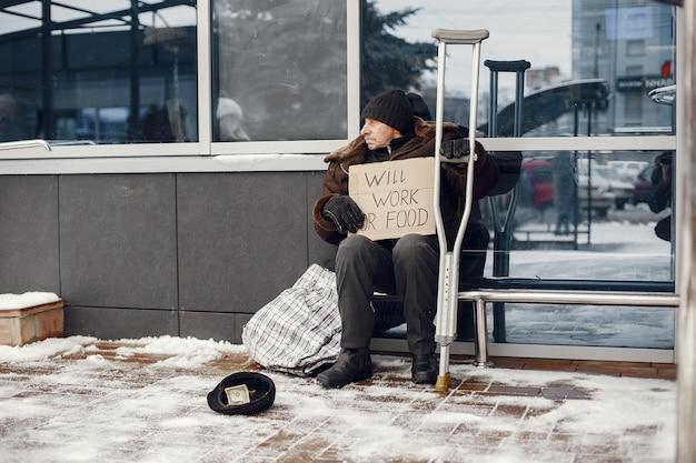 Obdachlose sitzen in der nähe des gebäudes.