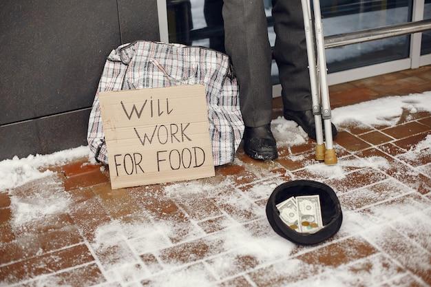 Obdachlose stehen in der nähe des gebäudes.