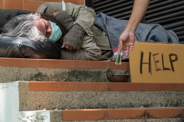 Obdachlosen am straßenrand geld geben.