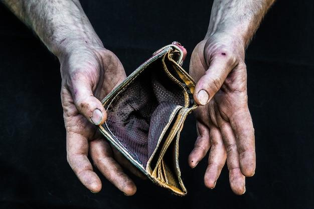 Obdachloser armer mann der schmutzigen hände mit leerer geldbörse in der modernen kapitalismusgesellschaft