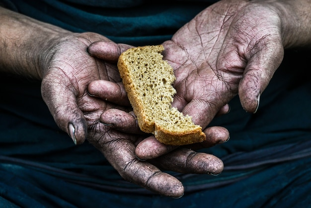 Obdachloser armer mann der schmutzigen hände mit stück brot in der modernen kapitalismusgesellschaft